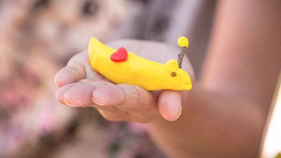 A person holds a toy banana slug